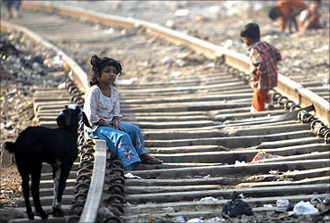 A girl sits on a rail track.
