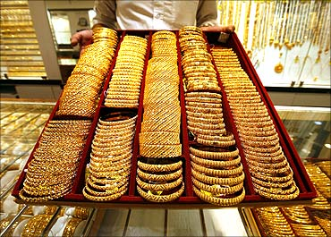 A salesman displays a tray of gold bangles.