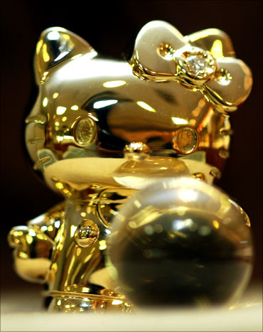 A tiny 18-karat gold Hello Kitty doll is displayed.