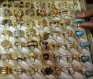 A Jordanian adjusts gold rings at his shop in Amman's gold market.