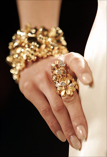 A model poses wearing gold jewellery.