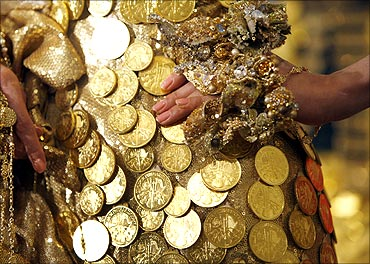 A model in a golden dress decorated with 325 Austrian gold coins, poses for photographers.