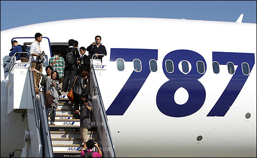 Passengers take pictures as they board the plane at Narita airport in Narita, east of Tokyo