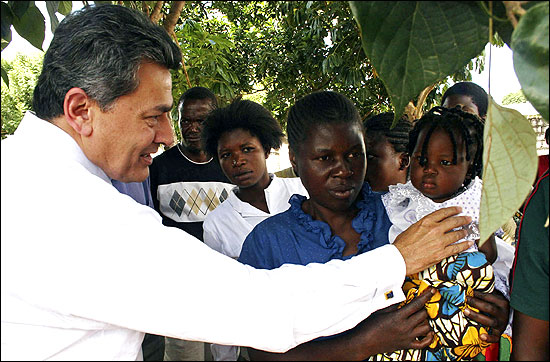 Rajat Gupta greets a child at a clinic in Lusaka.