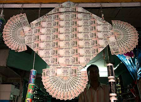 An kite maker stands besides a kite made of notes of the Indian currency in New Delhi.