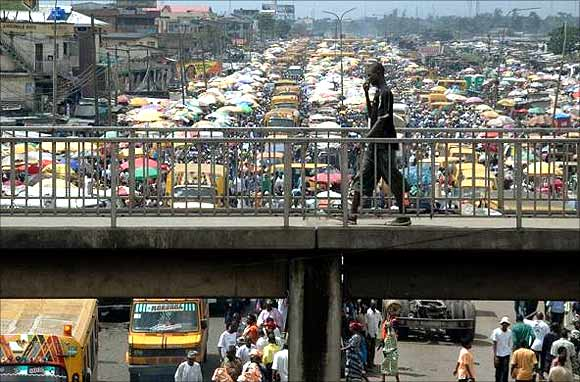 A man walks on a pedestrian bridge overlooking traffic in Lagos, Nigeria.