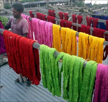 A worker arranges coloured skeins of yarn