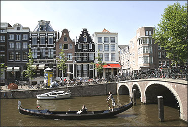 A woman rows her gondola through the canals of central Amsterdam.