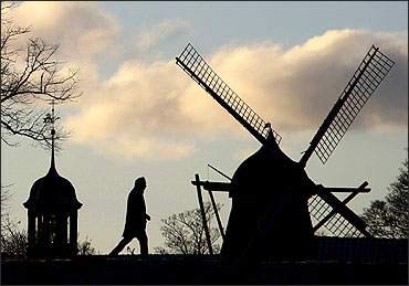 A man walks past a windmill in Kastellet park in Copenhagen.