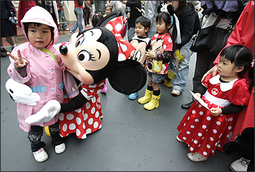 A Japanese girl poses with Disney character Minnie Mouse at Tokyo Disneyland.