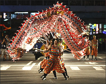 Participants perform a dragon dance during a Hungry Ghost Festival parade along the streets of Keelung, northern Taiwan.