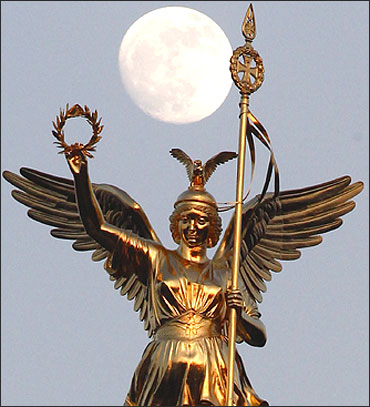 The moon is pictured beside the Golden Victoria on top of the victory column in Berlin.