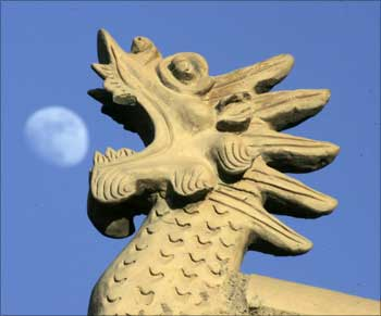Chinese architecture style dragon head is seen as the moon rises at Jiayuguan Pass, China.