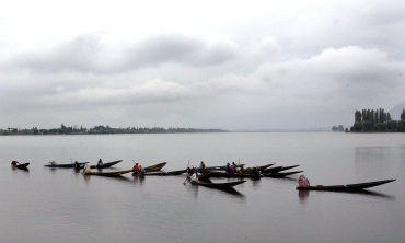 Kashmiri women row their boats on a cold day in Srinagar.
