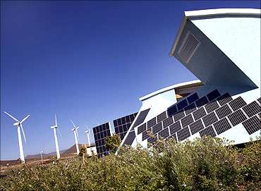 The solar panels of a bioclimatic house are seen next to windmills.