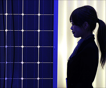 A woman is silhouetted next to a solar panel display by solar module supplier in Tokyo.