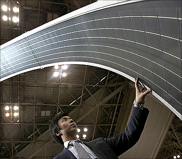 A man touches a display of the Global Solar Energy's PowerFLEX BIPV flexible solar module in Tokyo.