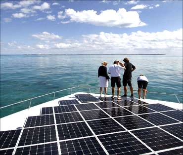 People stand on the world's largest solar-powered boat in Cancun.