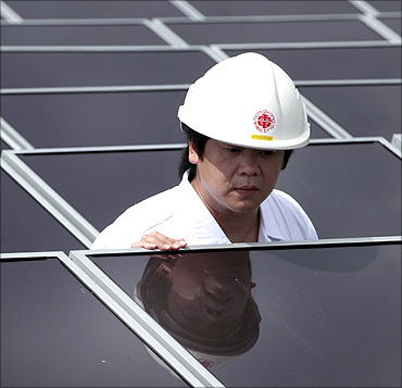 A worker checks solar panels on the roof of a building in Hong Kong Electric Lamma island power unit