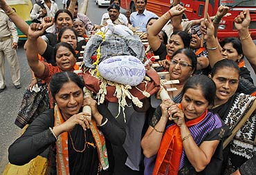 Supporters of Bharatiya Janata Party (BJP) carry an effigy depicting inflation during a mock funeral procession.