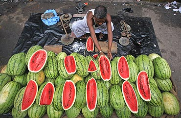 A vendor arranges watermelons for sale along the side of a road in Kolkata.