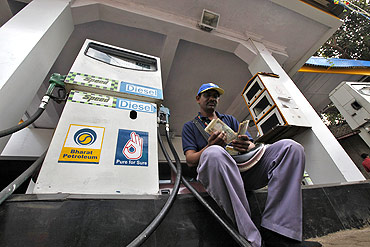 A worker counts Indian currency at a fuel station in Mumbai.