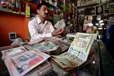 A shopkeeper counts Indian currency notes inside his shop in Jammu.