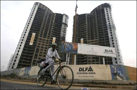 A man cycles past the construction site of a residential apartment building by DLF Ltd.