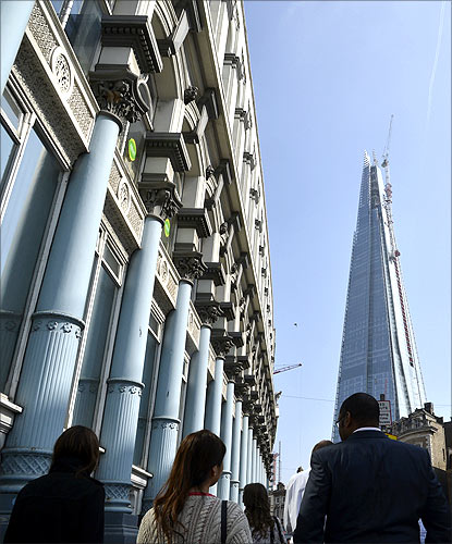 Pedestrians walk near the Shard building in central London.