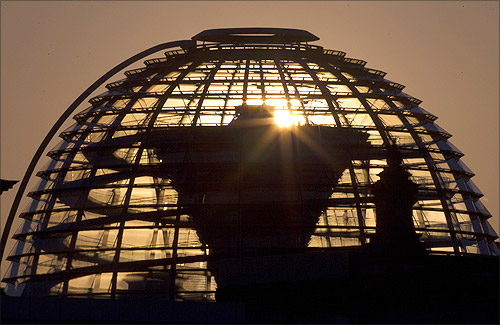 The sun rises behind the cupola of the Reichstag building, the seat of the German lower house of parliament, on a sunny cold day in Berlin.