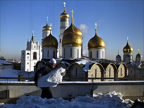 A worker cleans snow from a roof in front of the domes of the several several churches and cathedrals inside Moscow's Kremlin.
