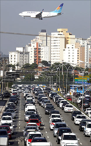 An airplane prepares to land over a jammed highway during a normal weekday at Congonhas Airport, one of Sao Paulo's two busy airports.