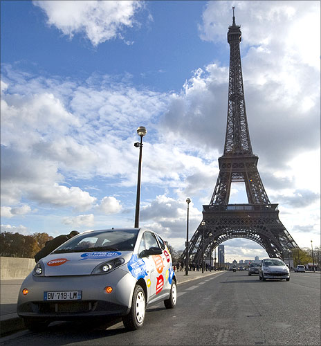 A Paris Autolib' electric car is parked next to the Eiffel tower.