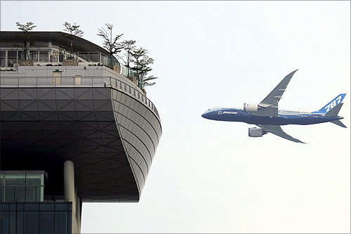 A Boeing 787-8 passenger jet flies near the skypark of the Marina Bay Sands hotel during a demonstration flight in Singapore.