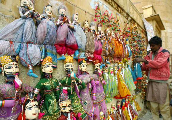 An artisan arranges puppets for sale at the Jaisalmer Fort at Jaisalmer, Rajasthan. The Jaisalmer Fort was built in 1156 AD by the Bhati Rajput ruler Rawal Jaisal.
