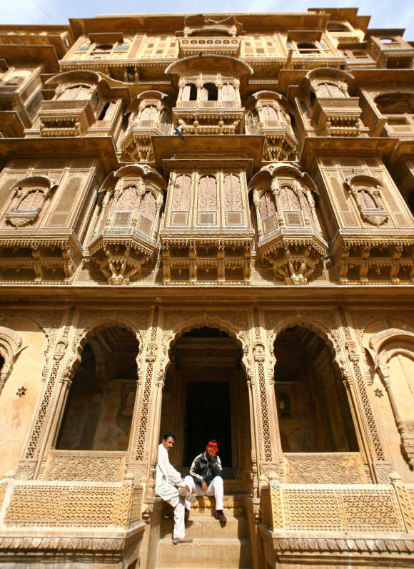 People sit in front the 'Patwa Haveli' in Jaisalmer, Rajasthan. The Patwa Haveli is a cluster of five small havelis and are also known as the mansion of brocade merchants.