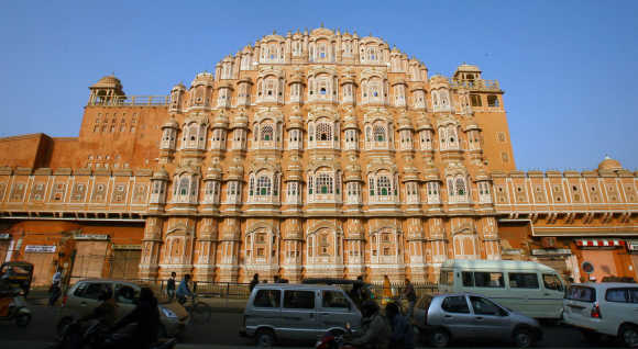Commuters move in front of 'Hawa Mahal' also known as 'Palace of Winds' in Jaipur, Rajasthan. Hawa Mahal was built in 1799 by Maharaja Sawai Pratap Singh, designed by Lal Chand Usta in the form of the crown of Hindu Lord Krishna and have five stories and is constructed of red and pink sandstone. The side facing the street outside the palace complex has 953 small windows.