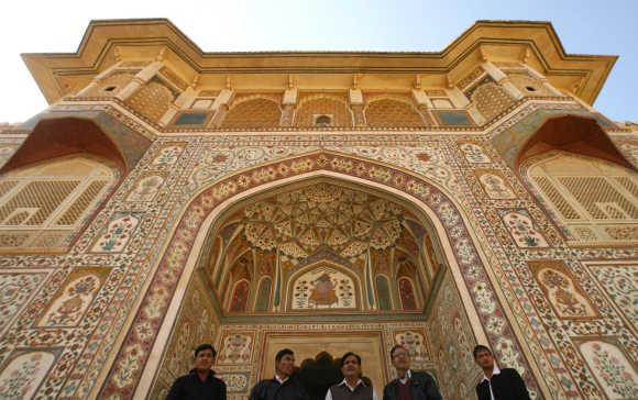 Tourists stand at the Amber Fort in Jaipur, Rajasthan. The structure known as Amber fort contains several spectacular buildings and is actually the palace built by Raja Man Singh I who ruled from 1590-1614 AD.