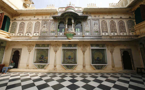A tourist rests inside the City Palace in Udaipur, Rajasthan. The City Palace contains many antique articles, paintings, decorative furniture and utensils.