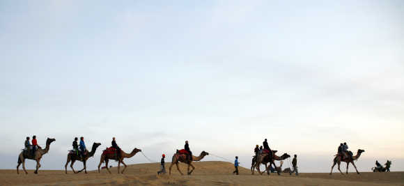 Tourists take camel ride on the Thar Desert in Jaisalmer, Rajasthan. The Thar Desert, also known as the Great Indian Desert, is a large arid region in the northwestern part of the subcontinent.