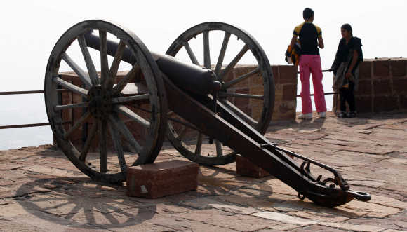 Tourists stand beside medieval cannons at the Meharangarh Fort in Jodhpur, Rajasthan.