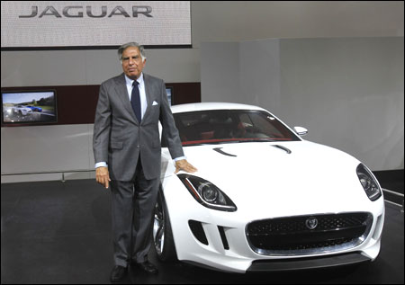 Ratan Tata poses with Jaguar's newly launched C-X16 car during India's Auto Expo, in New Delhi on January 5, 2012.