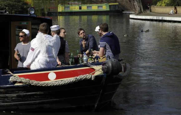 People sit in a boat at Little Venice on the Regent's Canal, in north London. The 14.5-kilometre Regent's Canal is one of the capital's best-kept secrets. Largely hidden behind buildings, the line sneaks its way through a rich collage of urban landscapes. Starting at the houseboats of Little Venice, it wends its way through Camden Lock and fashionable East London, and bypasses the site of the London 2012 Olympic Games before ending in Limehouse Basin.