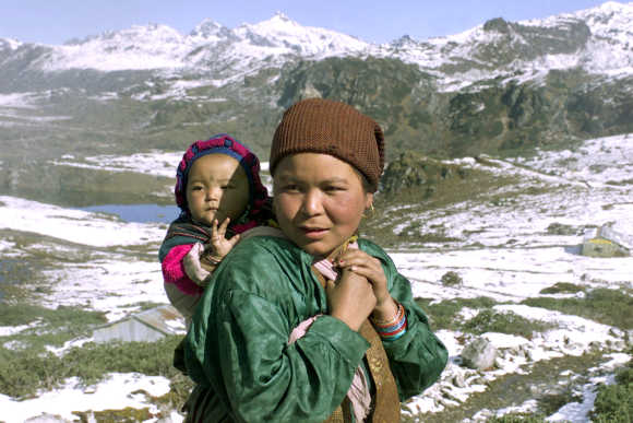 A Monpa tribal woman carries her child near the border with China in Sella, located at a height of 13,000ft in Arunachal Pradesh.