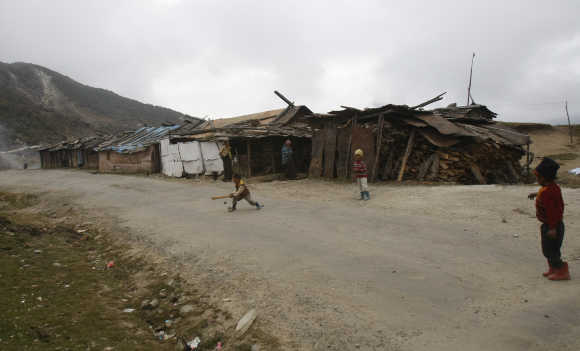 Children of labourers play cricket on a street near a stone crusher plant in Tawang in Arunachal Pradesh.