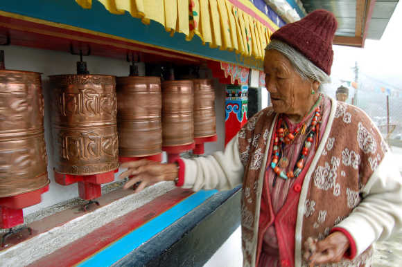 An elderly lady of the Manpa tribe spins prayer wheels at a monastery in Tawang in Arunachal Pradesh near the border with China.