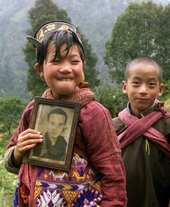 A Monpa tribal girl wearing traditional dress poses with a photograph of a Buddhist priest as her brother looks on in Tawang in Arunachal Pradesh.