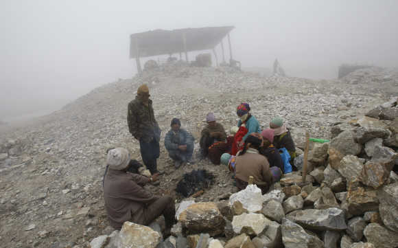 Workers warm themselves around a fire on a cold foggy day at a stone crusher plant in Tawang in Arunachal Pradesh.