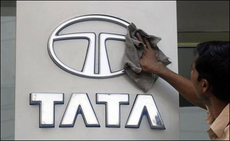 A worker cleans a Tata Motors logo outside its showroom in Hyderabad.