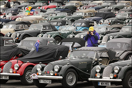 An enthusiast takes photographs amongst a large collection of Morgan sports cars.
